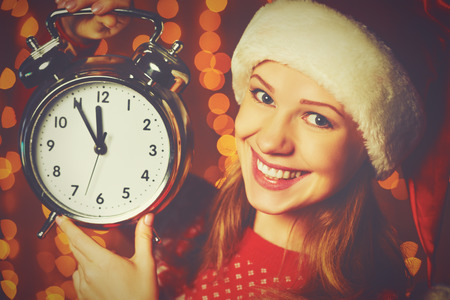 hat new year happy new year festive: Merry Christmas! Cheerful woman in a Christmas hat with alarm clock