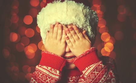 어린 소녀는 크리스마스의 기적과 선물의 기대에 눈을 그녀의 손을 폐쇄