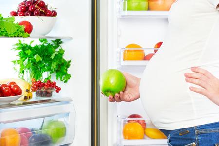 embarazada feliz: la nutrici�n y la dieta durante el embarazo. Mujer embarazada que se coloca cerca del refrigerador con frutas y verduras
