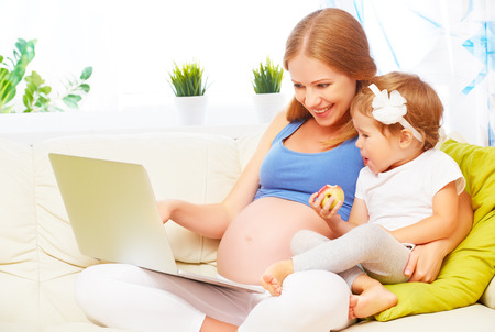 Happy family pregnant woman and child  with a laptop on the sofa at home