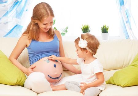 familia feliz en previsión de la bebé. Madre e hija hijo embarazadas colores de pintura en el abdomen Foto de archivo