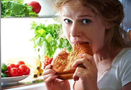comiendo: mujer come dulces en la noche para colarse en un refrigerador Foto de archivo