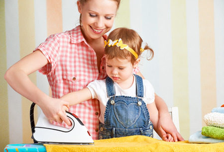 irons: happy family mother and baby daughter together engaged in housework iron clothes iron Stock Photo