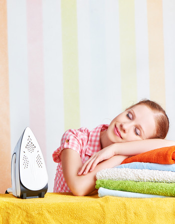 tired housewife fell asleep on the ironing board with iron Stock Photo