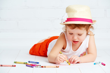 children hands: happy little artist  girl in a hat draws pencil lying on the floor Stock Photo