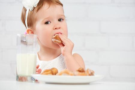 milk and cookies: happy child little girl eats cookies and milk
