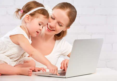 happy family mother and child baby daughter at home working on the computer Stock Photo - 44436209