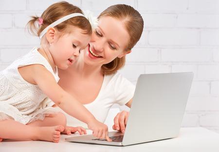niños ayudando: madre de familia feliz y pequeña hija hijo en casa trabajando en la computadora