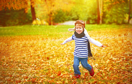 vintage children: happy child playing pilot aviator and dreams outdoors in autumn