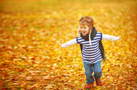 fly: happy child playing pilot aviator and dreams outdoors in autumn