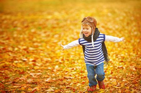 Dzieci: szczęśliwe dziecko bawiące się lotnik pilota i marzenia na zewnątrz jesienią