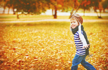 vintage travel: happy child playing pilot aviator and dreams outdoors in autumn