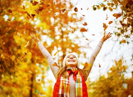 hojas parra: Feliz niña vomita hojas de otoño en el parque para un paseo al aire libre