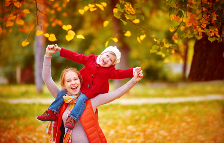 Autumn: familia feliz: la madre y la pequeña hija Juego de niños que abrazan en caminata del otoño en la naturaleza al aire libre