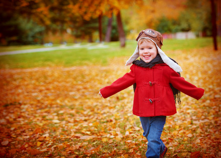 girl glasses: happy child playing pilot aviator and dreams outdoors in autumn