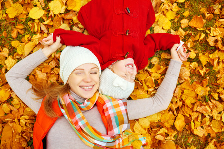 lifestyle outdoors: happy family: mother and child little daughter play cuddling on autumn walk in nature outdoors