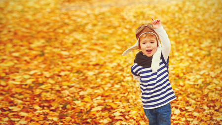 autumn leaves: happy child playing pilot aviator and dreams outdoors in autumn