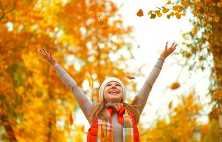 Gelukkig meisje werpt herfst bladeren in het park voor een wandeling buiten