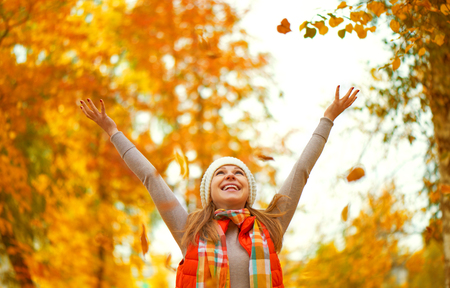 Happy girl throws up autumn leaves in the park for a walk outdoors