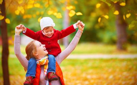 happy family: moeder en kind dochtertje spelen knuffelen op herfst wandeling in de natuur buiten