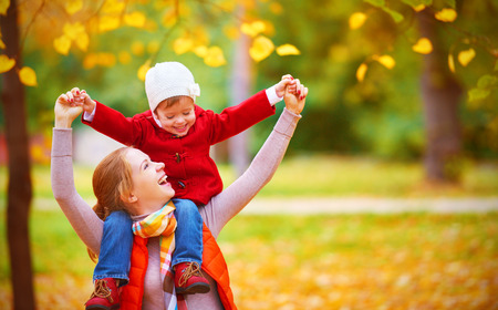 children playing outside: happy family: mother and child little daughter play cuddling on autumn walk in nature outdoors