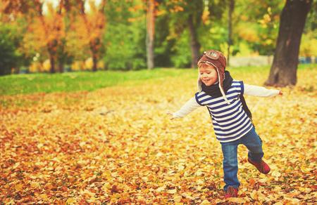piloto: niño feliz jugando aviador piloto y sueños al aire libre en otoño Foto de archivo