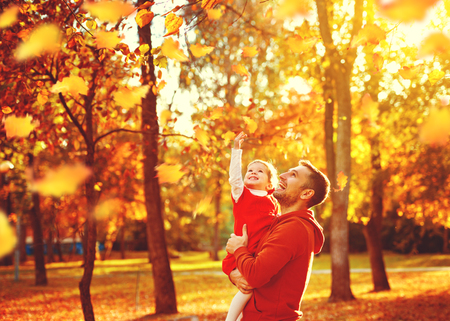 Happy family father and child daughter on a walk in the autumn leaf fall in park