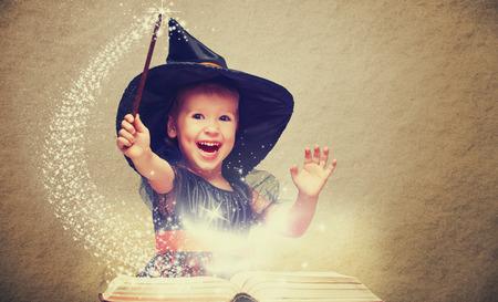 magia: Halloween. alegre pequeña bruja con una varita mágica y brillante libro conjure y se ríe.