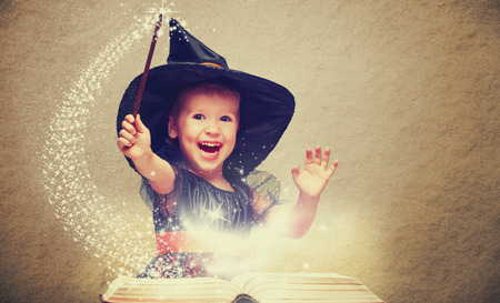 Halloween. cheerful little witch with a magic wand and glowing book conjure and laughs. Stok Fotoğraf - 45560726