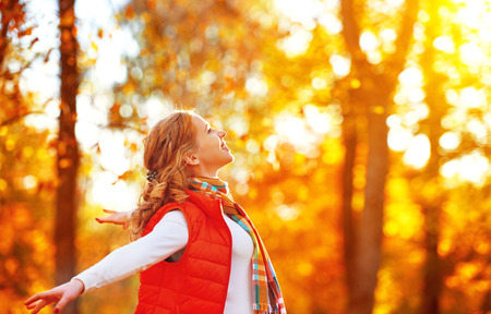 people: happy girl enjoying life and freedom in the autumn on the nature