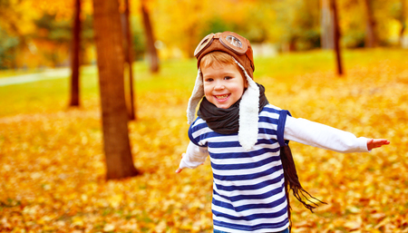 pilot: happy child playing pilot aviator and dreams outdoors in autumn