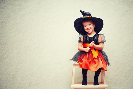Halloween. cheerful little witch with a magic wand conjure and laughs. Stock Photo