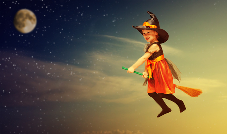 Halloween. Witch child flying on a broomstick at sunset the night sky.