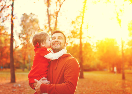 ni�as peque�as: Familia feliz. hija besando y abrazando a su padre en una caminata en la ca�da de las hojas de oto�o en el parque