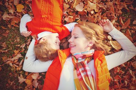 otoñales: familia feliz: la madre y la pequeña hija Juego de niños que abrazan en caminata del otoño en la naturaleza al aire libre