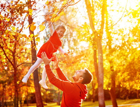 autumn in the park: Happy family Dad throws child daughter up on a walk in the autumn leaf fall in park