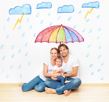 home plans: concept: the social protection of the family. family took refuge from the miseries and rain under an umbrella Stock Photo