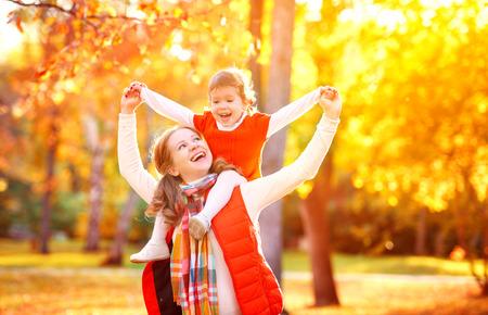 familia feliz: la madre y la pequeña hija Juego de niños que abrazan en caminata del otoño en la naturaleza al aire libre