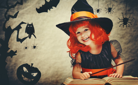calabazas de halloween: Halloween. alegre peque�a bruja con una varita m�gica y el conjure libro y risas. Foto de archivo