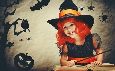 Halloween. vrolijke kleine heks met een toverstaf en het boek toveren en lacht.