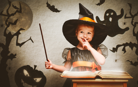 party dress: Halloween. cheerful little witch with a magic wand and the book conjure and laughs. Stock Photo