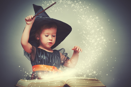 vintage children: Halloween. cheerful little witch with a magic wand and glowing book conjure and laughs.