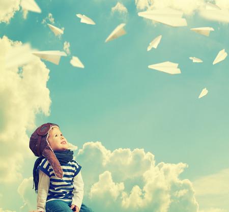 Gelukkig kind droomt ervan om een pilot-vlieger en speelt met vliegtuigen in de lucht