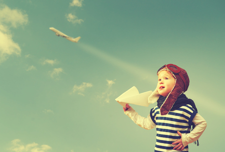 Happy child dreams of becoming a pilot aviator and plays with planes in the sky