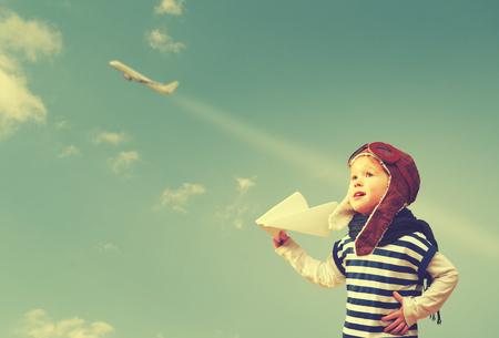 Niño feliz sueña con convertirse en un piloto aviador y juega con los aviones en el cielo Foto de archivo - 45560819