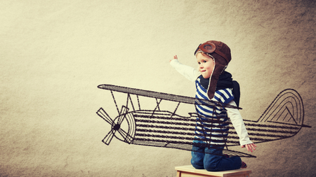 Happy baby dreams of becoming a pilot aviator and plays with planes on background wall of house