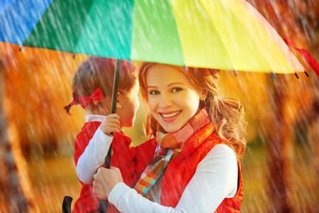 lluvia: Feliz madre de familia y su hija niño con color arco iris paraguas bajo la lluvia en la naturaleza