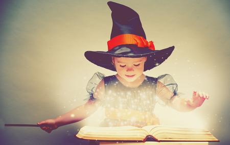 Halloween. vrolijke kleine heks met een toverstokje en gloeiende boek toveren en lacht.