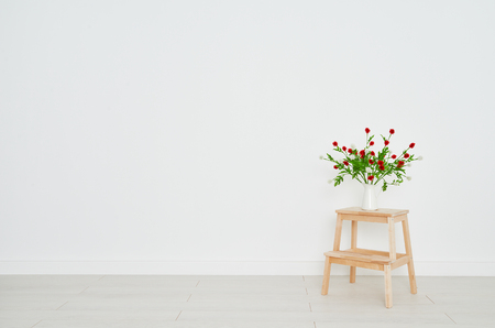 concept of a bouquet of flowers on a stepladder on the background white brick wall in an empty room