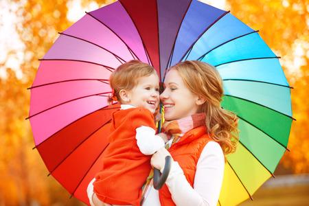 Счастливая семья мама и ребенок дочь радуги цветной зонтик под дождем на природе